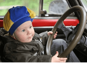 image shows a baby in the drivers seat of a vehicle