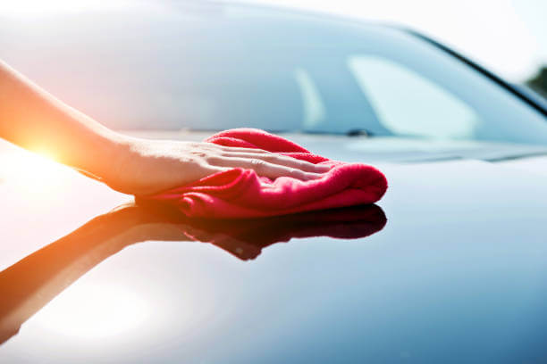 image depicts an individual wiping down a car