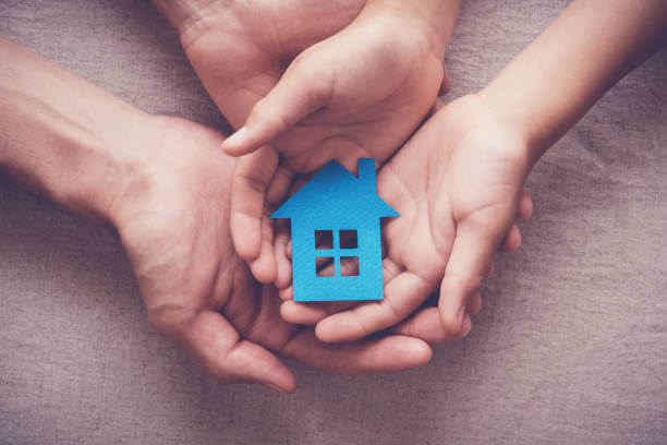 image shows hand holding a cutout of home