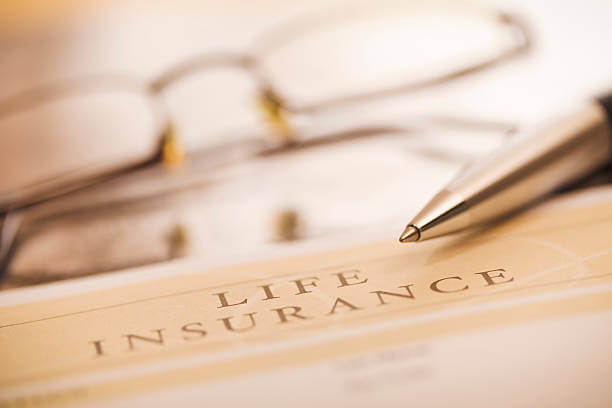 image shows a life insurance document with a pen and eyeglasses
