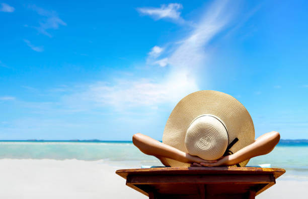 image shows lady with sunhat sitting on the beach in the sun