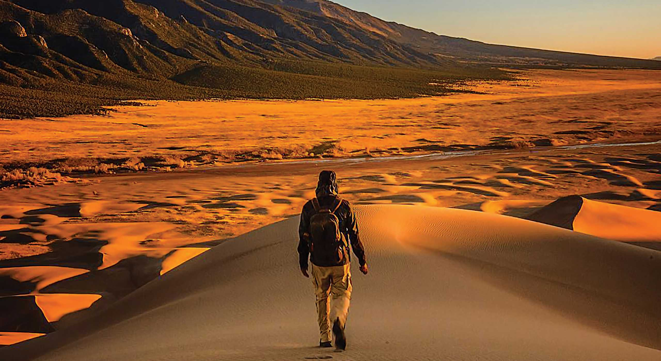 image shows man walking in the sand In Alamosa, CO