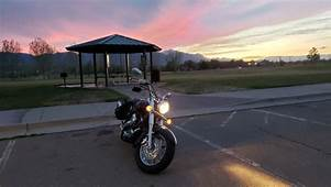 image depicts a motorcycle overlooking a sunset