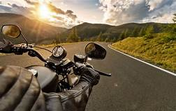 image depicts a motorcycle rider going down a windy mountain road