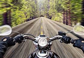 image depicts a motorcycle riding down a long narrow road