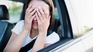 image shows lady covering her face, depicting she doesnt have car insurance
