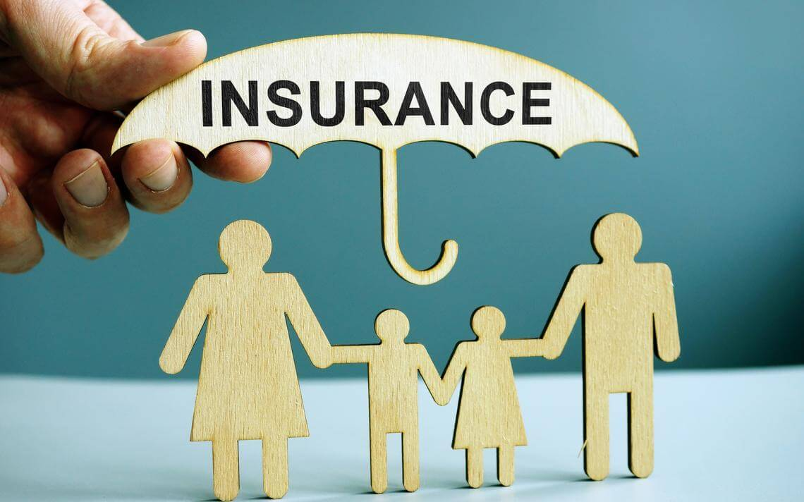 Picture of an umbrella with the word insurance on it, over a family